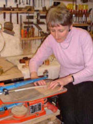 Sue Kane in the workshop cutting silver sheet.